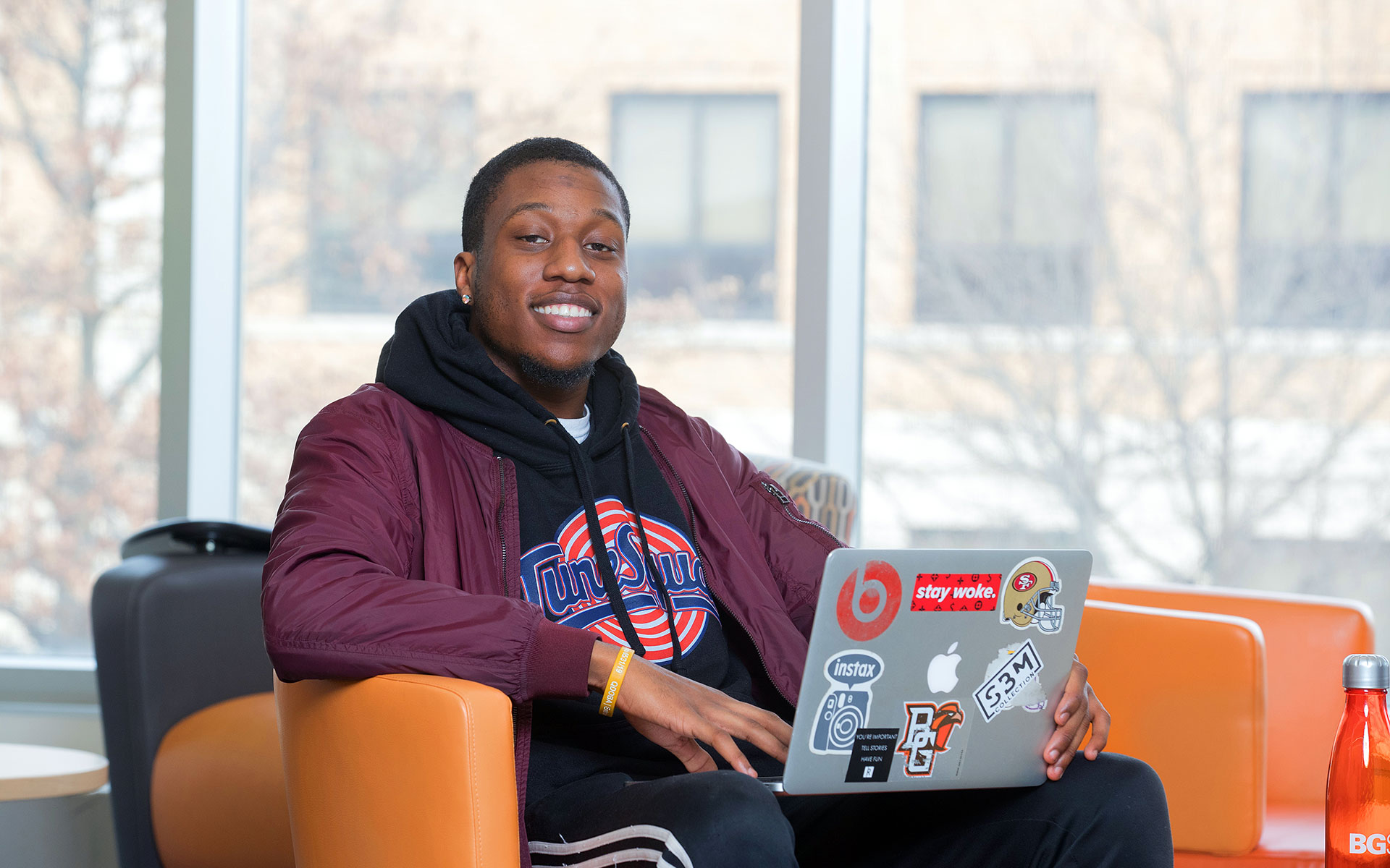 Student using laptop in union smiling at camera